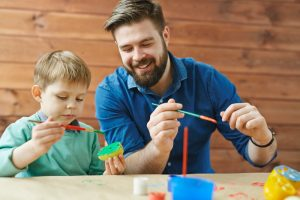 Smiling bearded young man in blue denim shirt paints fruit with a child