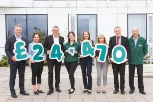 A group of people hold green numbers £24,470