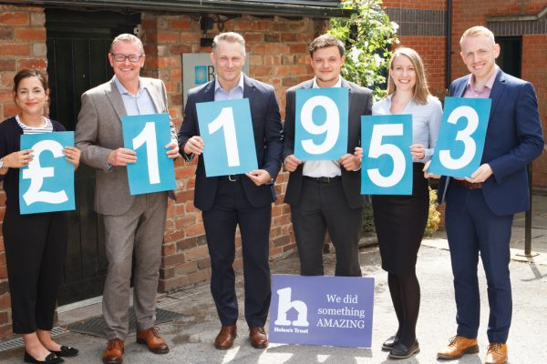 Six people stood in a row holding cards showing the total raised during the Helen's Trust Free Wills Month