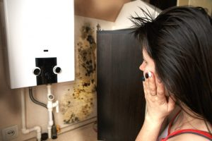 A Woman Looks At Mould On Her Kitchen Wall After Her Landlord Does Not Reply To An Improvement Notice