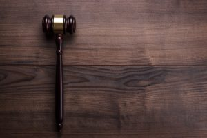 Judge's gavel laid on a dark wood table