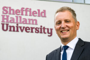 Solicitor Giles Searby Stood In Front of Sheffield Hallam University Sign